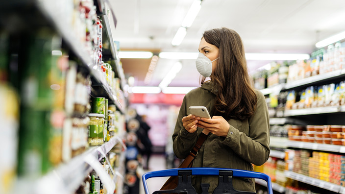 Frau mit Atemschutzmaske checkt Supermarktregal