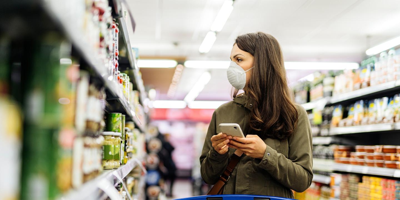 Frau mit Schutzmaske beim Einkaufen im Supermarkt