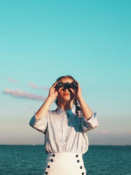 junge Frau schaut durch ein Fernglas