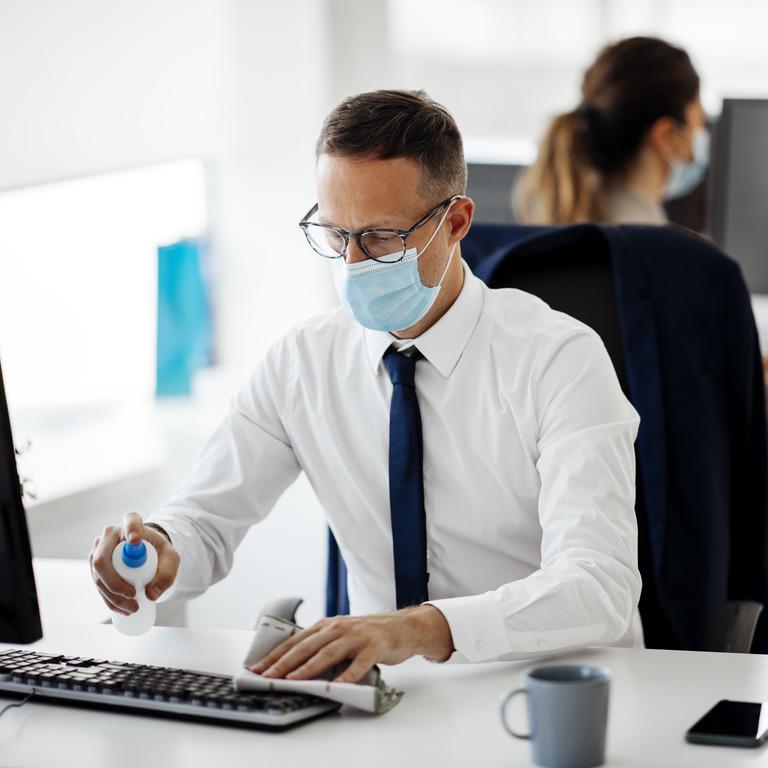 Angestellter sitzt mit Mundschutz vor seinem Büro-Rechner und desinfiziert ihn
