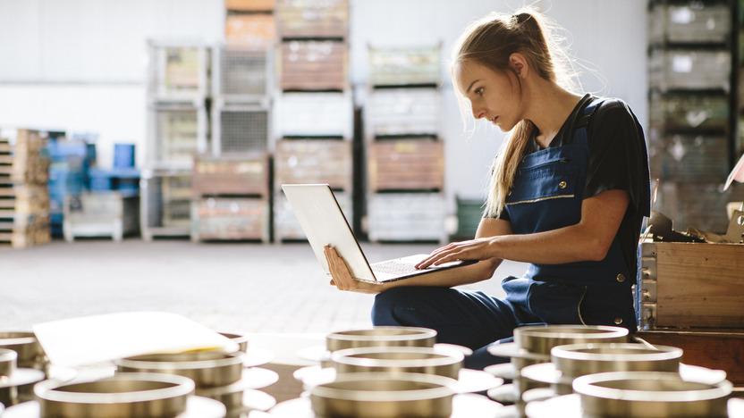 Auszubildende sitzt mit einem Laptop in einer Werkhalle