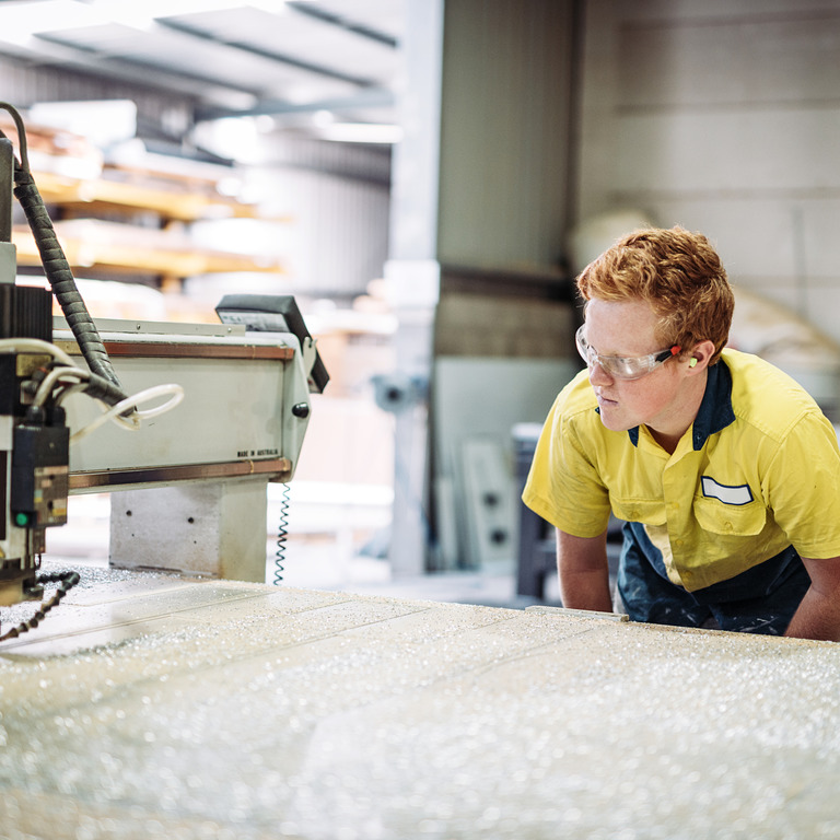 Rothaariger junger Mann beugt sich in gelber Arbeitskleidung über eine Werkbank
