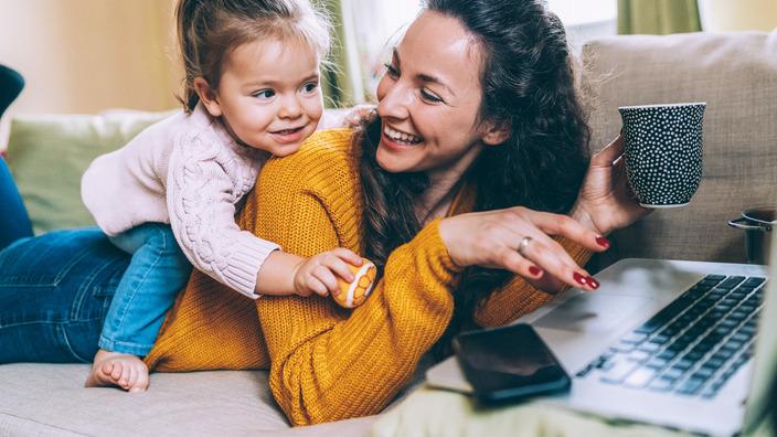 Eine Frau liegt mit einer Kaffeetasse in der Hand und einem Laptop bäuchlings auf der Couch, während ein kleines Mädchen aus ihrem Rücken sitzt