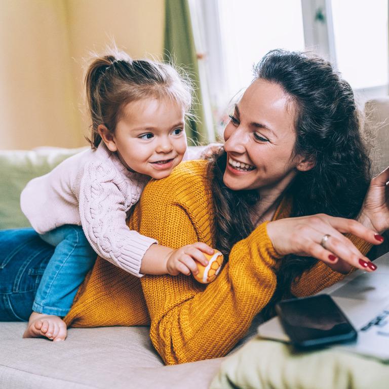Frau liegt mit ihrem Laptop bäuchlings auf dem Sofa, ihre kleine Tochter sitzt auf ihrem Rücken
