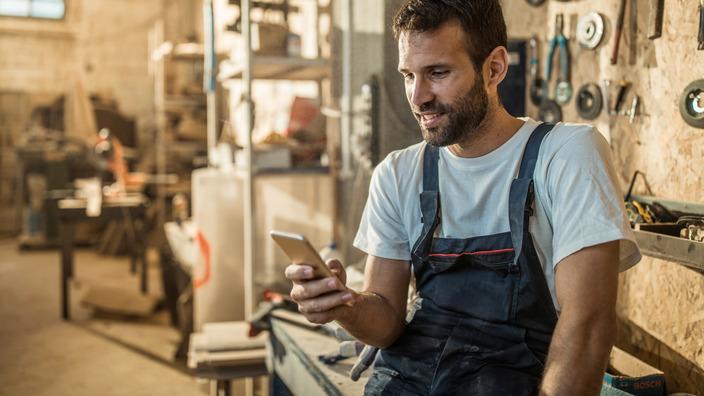 Ein männlicher Handwerker in Arbeitskleidung sitzt auf einer Werkbank und schaut auf sein Smartphone
