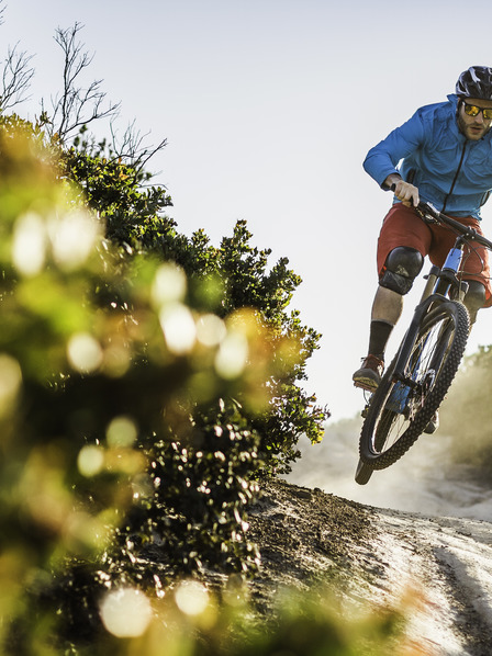 Mann mit Helm und Schutzbrille fährt mit Mountainbike einen Berg runter