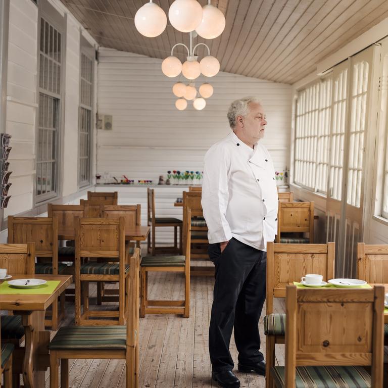 Restaurantbesitzer steht im leeren Saal und schaut aus dem Fenster.