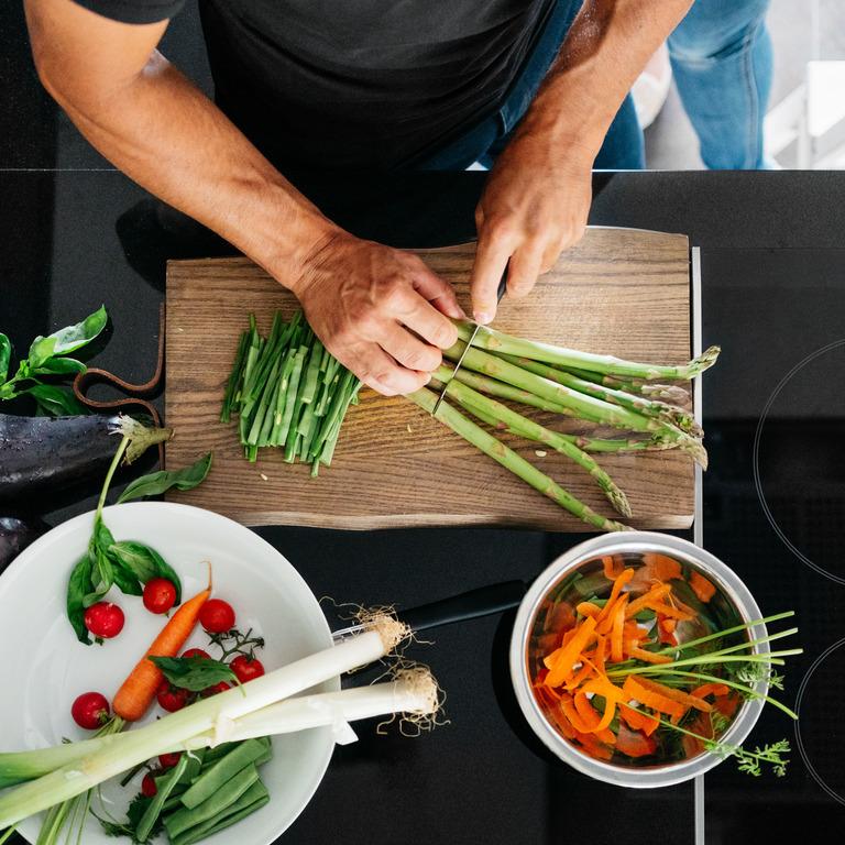 Mann steht in seiner Küche und schneidet Frühlingszwiebeln