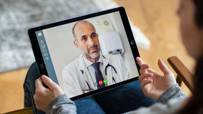 Arzt im weißen Kittel in einem Videoanruf auf einem Tablet