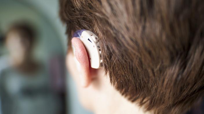 junger Mann mit Hörgerät