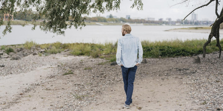 junger Mann geht gedankenversunken am Ufer eines Flusses entlang
