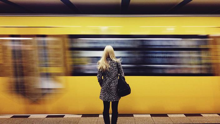 Frau steht alleine am Bahnsteig, während eine gelbe U-Bahn vorbeifährt