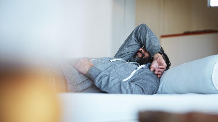 Mann liegt deprimiert auf einer Couch und hält den Arm vor sein Gesicht