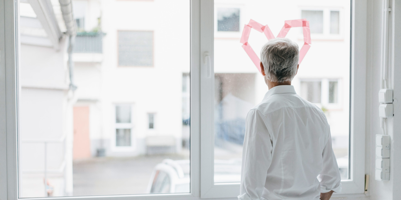 Mann schaut nachdenklich aus einem Fenster auf dem ein Herz klebt
