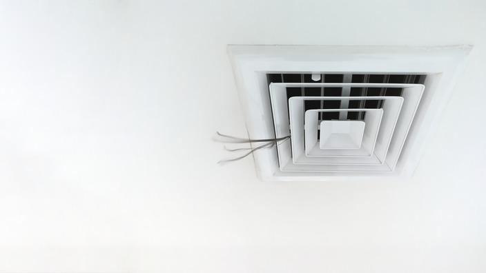 Aus einer Klimaanlage an der Decke eines Büros strömt Luft.
