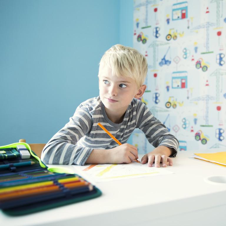 Grundschüler sitzt an seinem Schreibtisch und macht Hausaufgaben