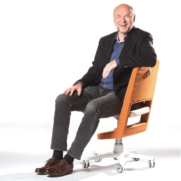 Martin Moll sitzt auf einem Bürostuhl