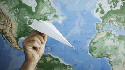 Hand hält Papierflieger vor Weltkarte