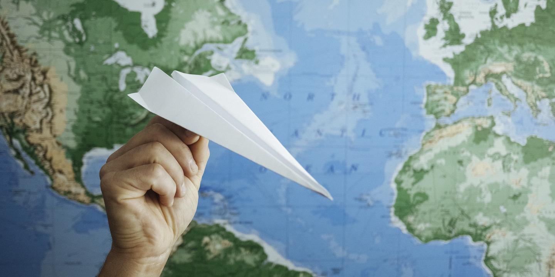 Papierflieger fliegt vor einer Weltkarte