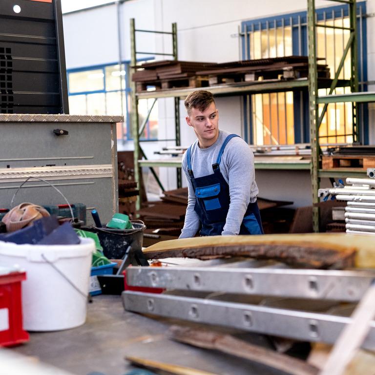 Junger Mann in Latzhose arbeitet in einer Lagerhalle.
