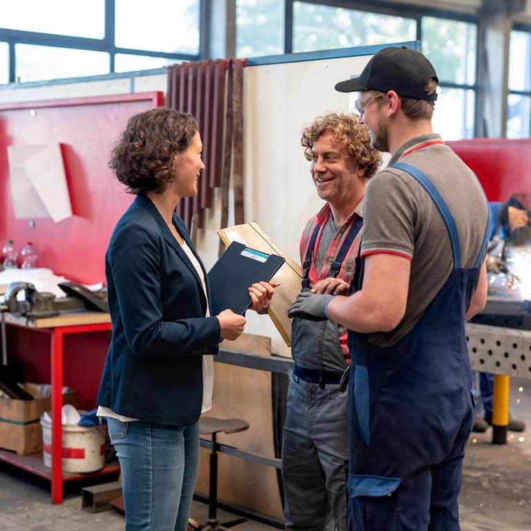 Weibliche Führungskraft spricht lachend mit Mitarbeitern.