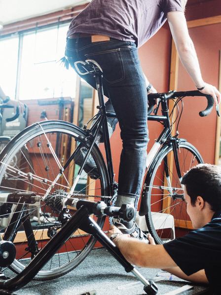 Mann sitzt auf einem Fahrrad, das Fahrrad ist in einem Gestell fixiert