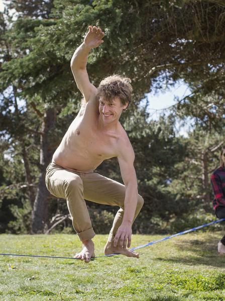 junger Mann beim Slacklinen im Park