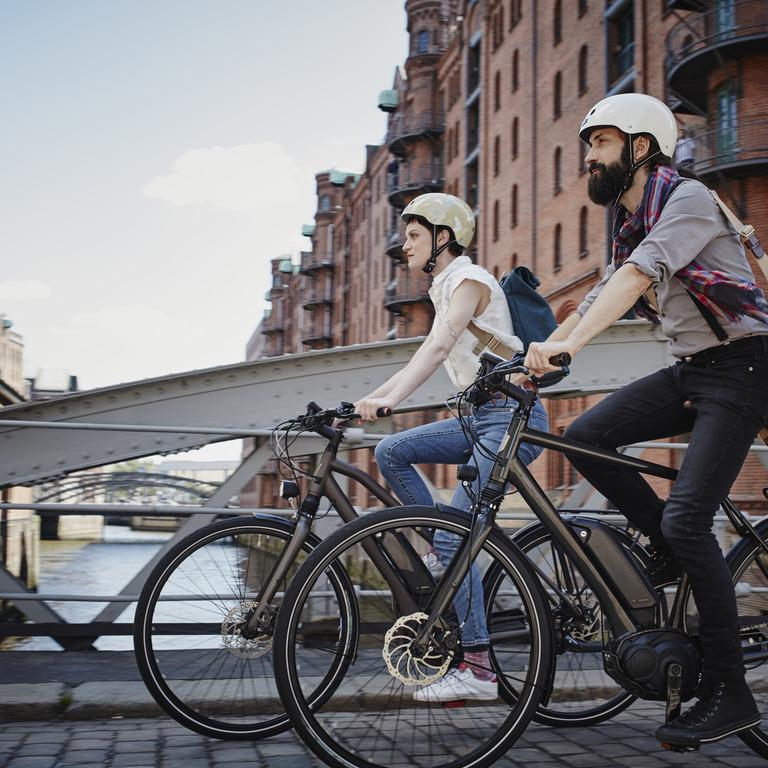 Junge Man und Frau fahren mit dem Fahrrad über die Brücke. Sie sind leicht angezogen und beide tragen einen Helm.