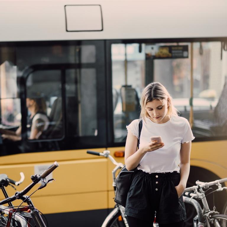 Junge Frau steht auf ihr Smartphone schauend vor einem gelben Bus