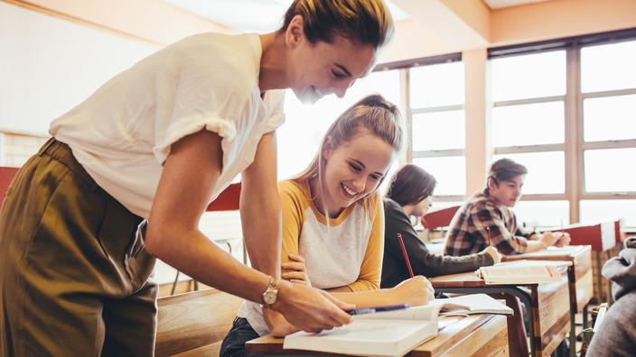 Lehrerin zeigt Schülerin etwas im Buch