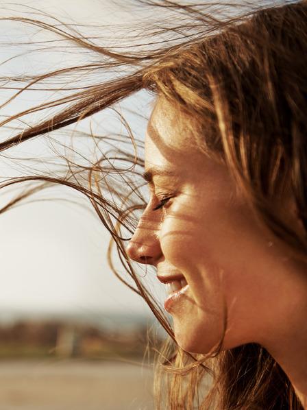 Frau mit wehendem Haar genießt den Wind und frische Luft