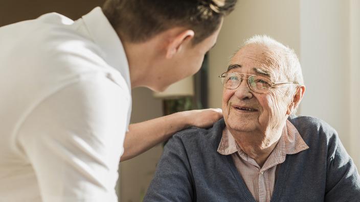 Pfleger legt einem Altenheim-Bewohner eine Hand auf die Schulter