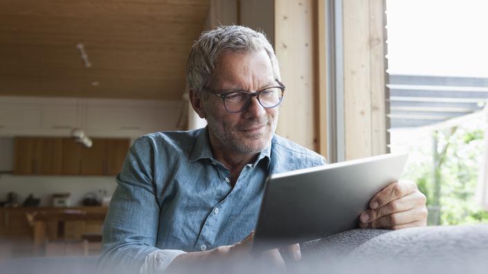 Mann sitzt auf einem Sofa vor einem Fenster und liest etwas auf seinem Tablet