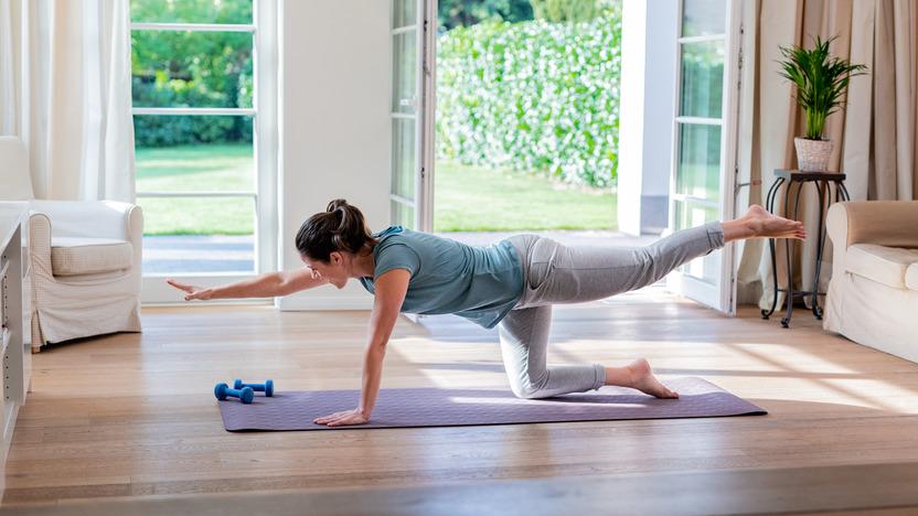 Frau macht Yoga zuhause bei geöffneter Terassentür