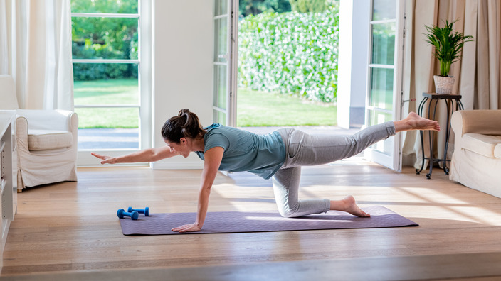 Frau ist im Vierfüßlerstand auf einer Gymnastikmatte und streckt gleichzeitig den rechten Arm und das linke Bein aus