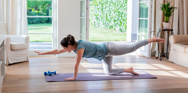 Frau kniet in ihrem Wohnzimmer auf einer Yogamatte und macht eine Yogaübung