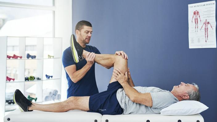 Physiotherapeut mobilisiert das rechte Bein eines Patienten