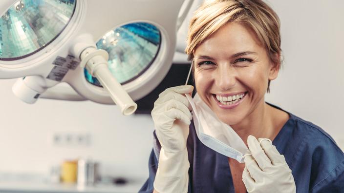 Zahnärztin nimmt ihren Mundschutz ab und lächelt