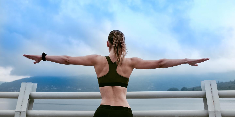 Frau in Sportklamotten streckt die Arme aus und blickt auf Berge in der Ferne.