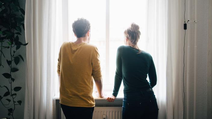 junges Paar, das aus einem Fenster schaut, von hinten
