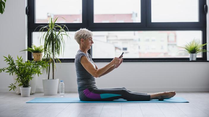 Eine Frau im Fitness-Outfit sitzt mit dem Tablet in der Hand auf einer Yogamatte