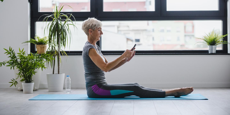 Frau hält ein Handy in der Hand und sitzt in Sportkleidung auf einer Yogamatte