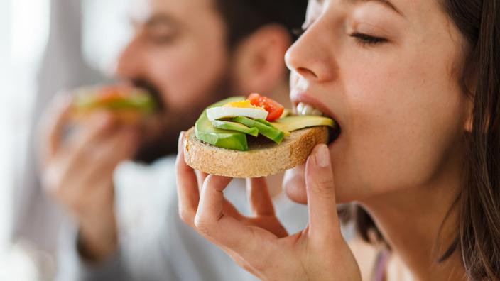 Ein junges Paar (Frau im Vordergrund) essen genüsslich ein Brot mit Avocado, Ei und Cherry-Tomaten belegt.