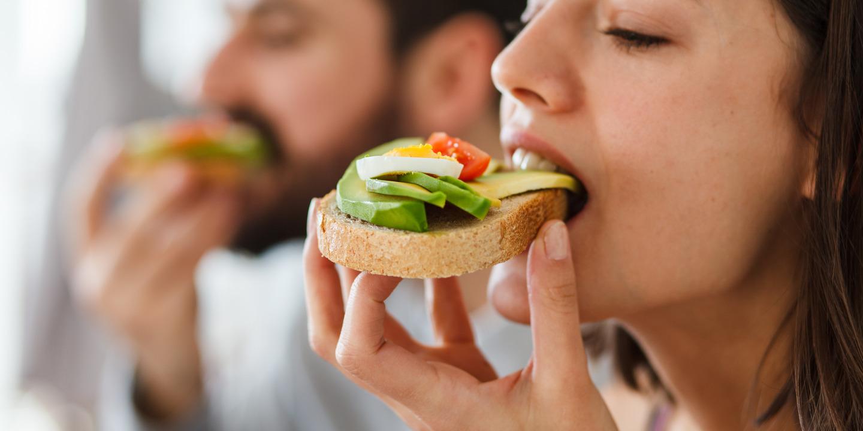 Frau und Mann beißen in belegtes Brot mit Avocado
