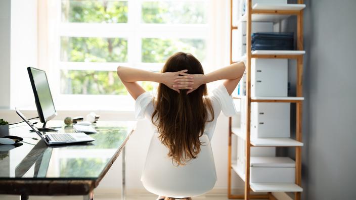 Frau entspannt auf dem Bürostuhl beim Blick aus dem Fenster.