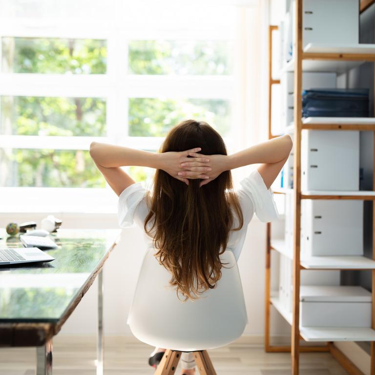 Rückansicht einer Frau, die sich auf einem Stuhl zurücklehnt