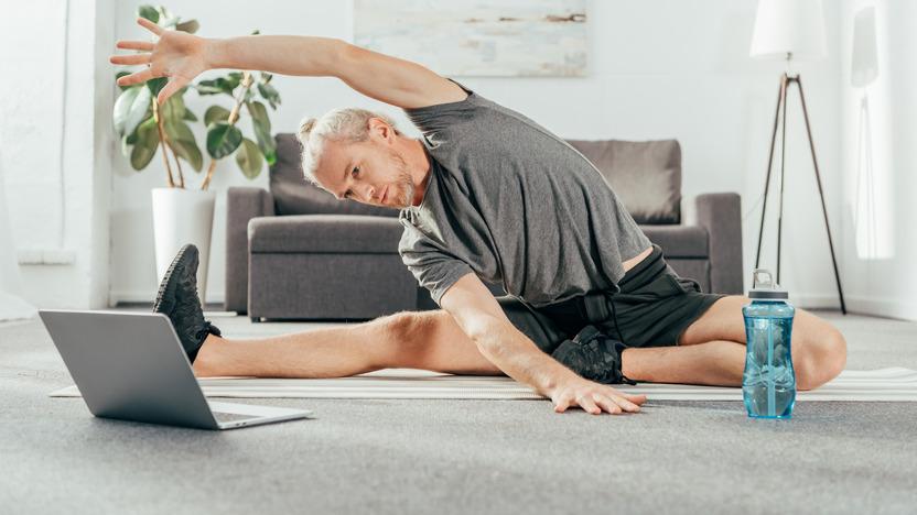 Mann in Sportkleidung macht Fitnessübungen vor einem Laptop