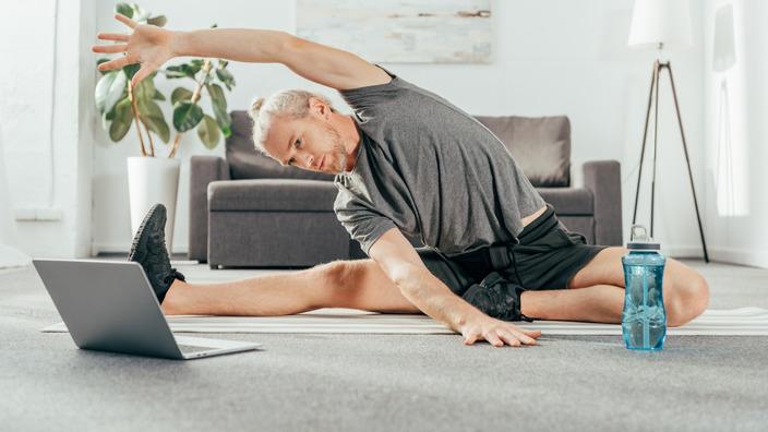 Ein Mann im grauen Fitness-Outfit führt eine Dehnübung vor dem Laptop aus