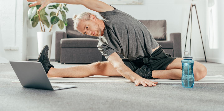 Mann dehnt seine seitliche Rumpfmuskulatur vor dem Laptop im Wohnzimmer