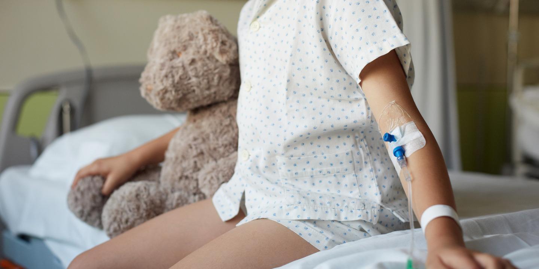 Kind sitzt in Palliativstation auf dem Bett mit Teddy im Arm.